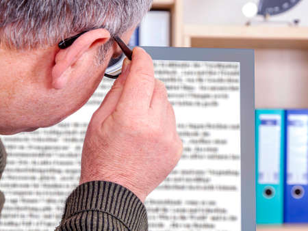 Man with glasses looking at screen Stock Photo