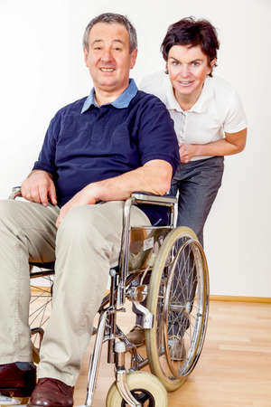 Woman pushing wheelchair Standard-Bild