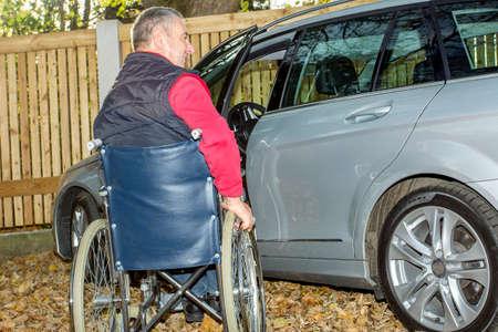 Mann im Rollstuhl im Herbst neben ihrem Auto