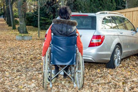 Frau in einem Rollstuhl im Fall nahe bei ihrem Auto