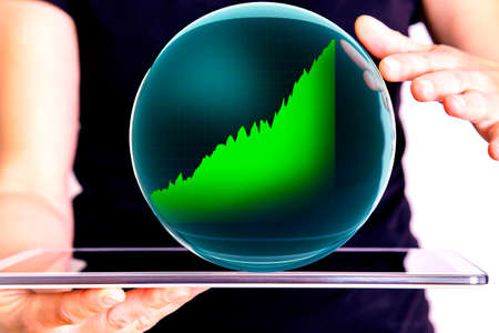 Hand holding tablet pc with glass globe and chart