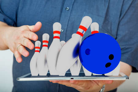 Man with tablet pc and bowling game