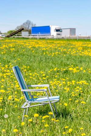 freely: Abandoned garden chair in flower meadow Stock Photo