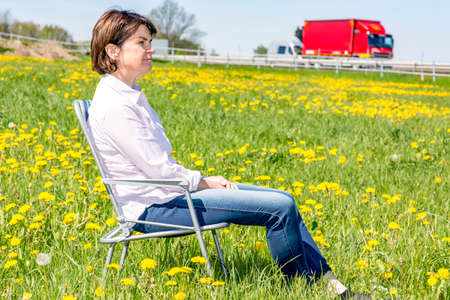 freely: Woman sitting on garden chair in a flower meadow