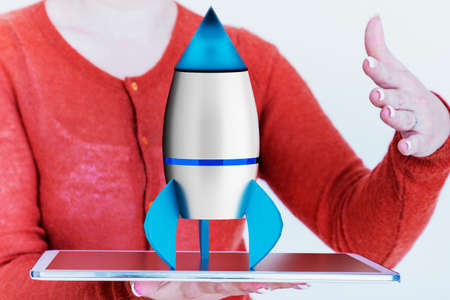 came: Woman holding tablet pc with rocket Stock Photo