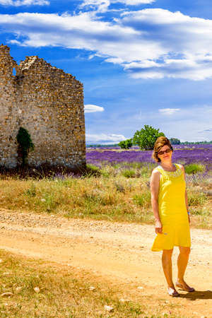 suns: Woman in lavender field in front of old ruin Stock Photo
