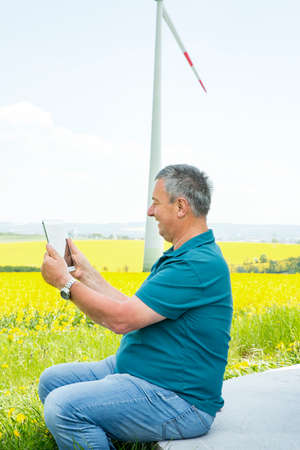 moulder: Man with tablet PC on the canola field with wind turbine