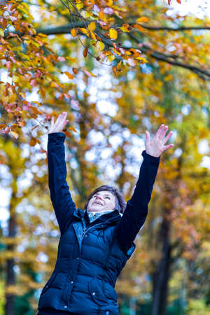 Woman stretches herself and hops with joy in the autumn wood Zdjęcie Seryjne