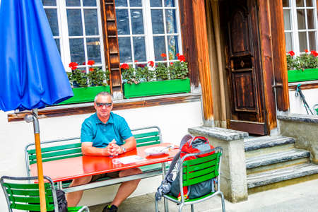 Man sitting on bench in front of house Фото со стока