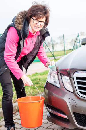 Woman cleans the car Stock Photo