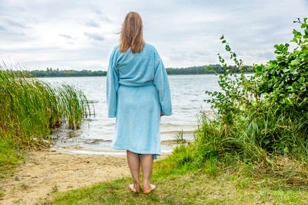 Young woman with bathrobe at the lake