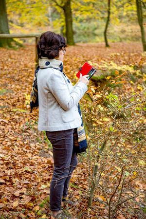 Woman is using her smartphone in the autumn forest