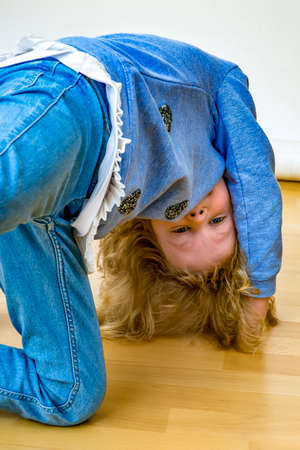 young blond girl is kidding on the floor