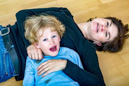床におばさんと若いブロンドの女の子をからかっています。 写真素材