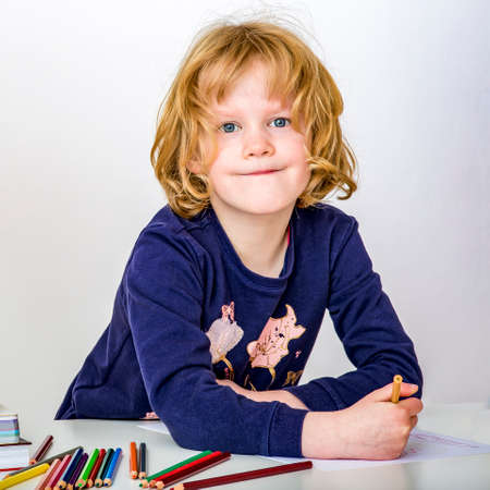 Girl with stack of books and crayons