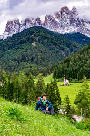 Woman in front of the church Ranui in South Tyrol