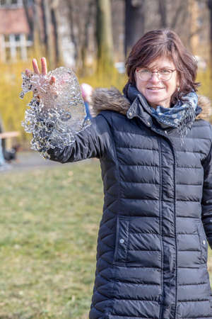 Woman holds ice piece in hand