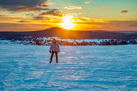 Woman in snow landscape with sunset