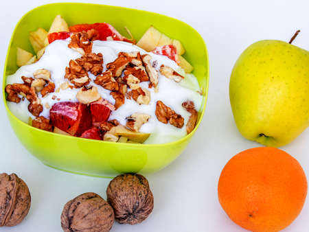 Fruit bowl with sliced apples oranges and nuts  Stock Photo