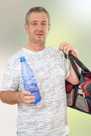 Man with water bottle and sports bag Stock Photo