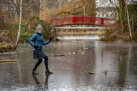 Woman on frozen pond in winter Stock Photo