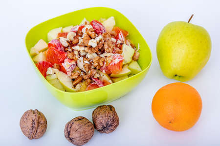 Fruit bowl with sliced apples oranges and nuts