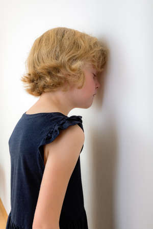 Child is standing with face to the wall Stock Photo