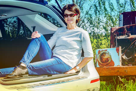 Woman sitting in trunk of car