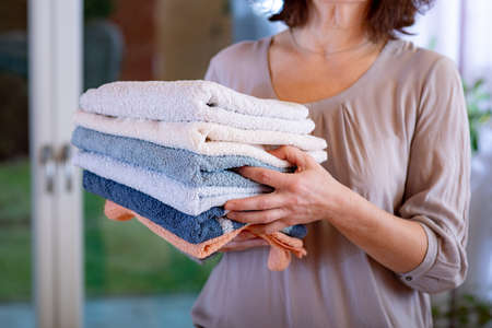 Woman carries towels Stock Photo