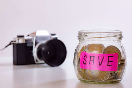Photo camera and glass with coins Stock Photo