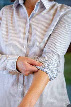 Woman is rolling up sleeves of her blouse Stock Photo