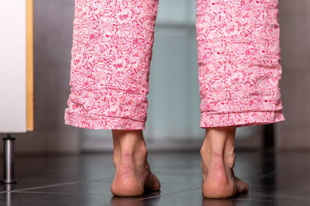 Woman is standing on the tile with bare feet Stock fotó