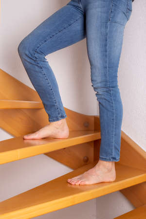 Woman with bare feet on the wooden stairs Stock fotó