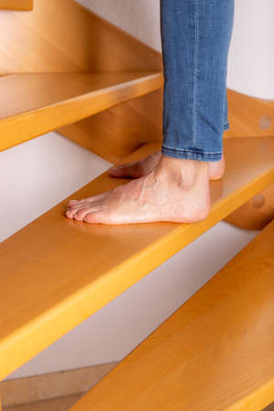 Woman with bare feet on the wooden stairs Banque d'images