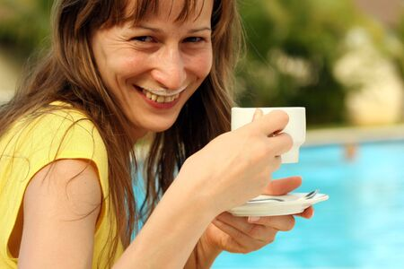 girl drinking a cup cappuccino by the pool photo