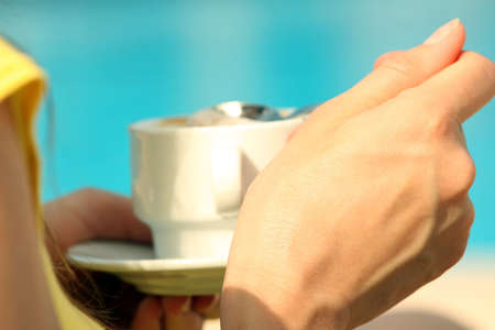 Woman drinking a cup cappuccino by the pool photo