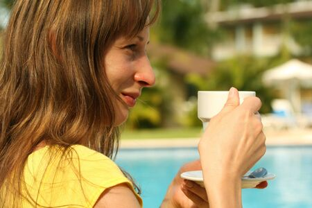 girl holding a cup coffee by the pool photo