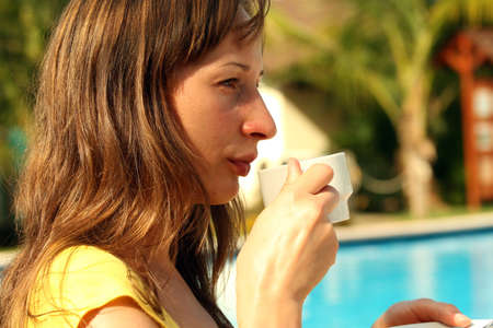 Woman by the pool with a cup coffee photo