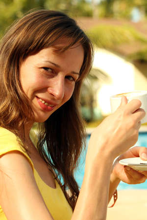 Girl with her coffee cup sitting by the pool photo