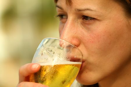 Girl drinking glass beer by the pool photo