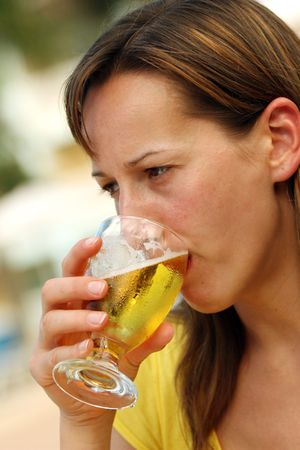 Girl drinking a glass cold and fresh beer photo