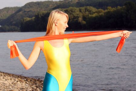 Woman trains with elastic band on the river beach photo