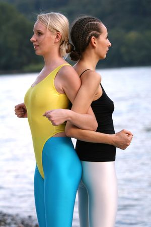 spandex: two young woman trains on the beach