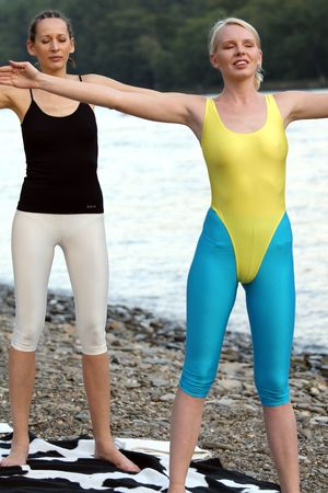 two women has breath exercises after training photo