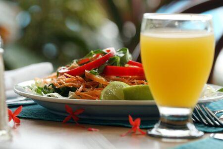 jus orange glazen: verse salade en glas sinaasappelsap op de tafel