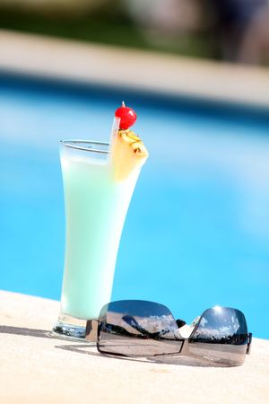 pool party: cocktail with sunglasses on the edge of the swimming pool Stock Photo