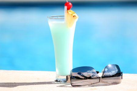 pool fun: fresh cocktail and sunglasses on the sun
