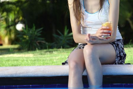 luxury party: girl holding cocktail by the swimming pool