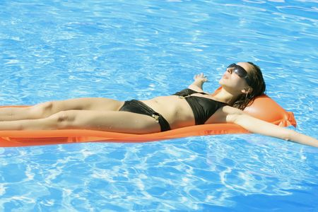swimming suit: woman swimming on mattress in pool Stock Photo