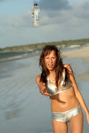 Woman in silver bikinis on the beach with bottle water Stock Photo - 2792131